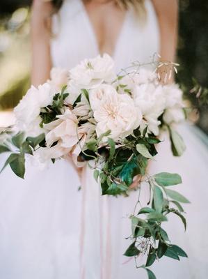 bride in v neck wedding dress neutral wedding bouquet greenery trailing vine fluffy flowers roses