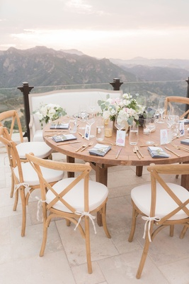 Wedding reception overlooking Malibu mountains canyons wood chairs white cushions low centerpiece