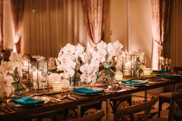 Wedding reception table wood with table runner, blue vases white orchid flowers in center