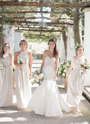 Bride in strapless wedding dress with bridesmaids in light color high neck pleated bridesmaid dress