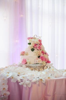 White cake with fresh roses on table of orchids