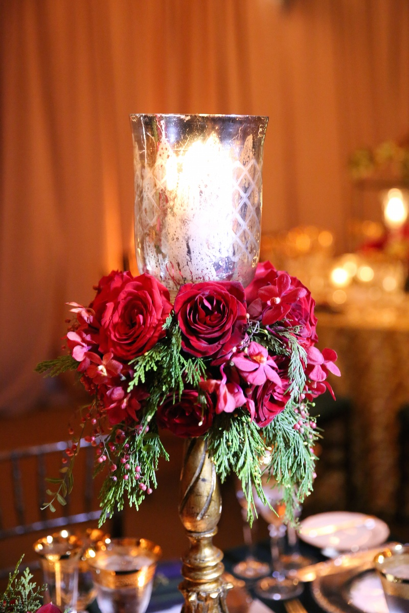 Christmas table decorations red and gold -  Gold Candlestick With Votive Red Roses Greenery On Reception Table Wedding Reception With Christmas Decorations