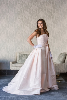bride in le spose di gio blush gown and overskirt and white gloves