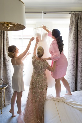 Mother of bride in sparkle dress helping bride in slip and other daughter in pink robe with dress