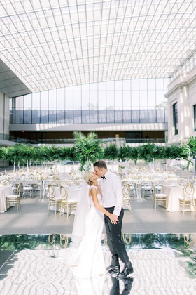 bride and groom wearing dress shirt without jacket kiss on mirror dance floor before guests arrive