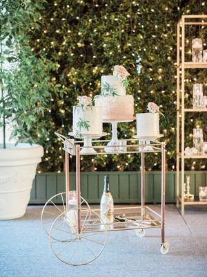 wedding cakes on pedestal bar cart champagne hedge wall string lights