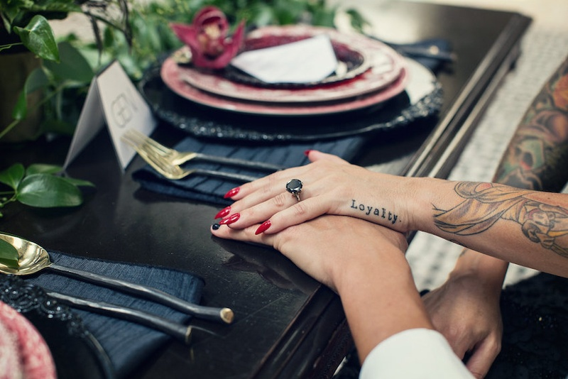 Bride with a round black diamond engagement ring, red nails, Loyalty tattoo on hand