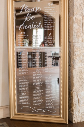 Wedding reception please be seated calligraphy seating chart gold frame white lettering by last name