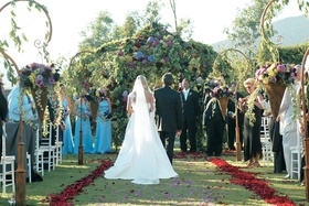 Garden ceremony with floral archway and petals