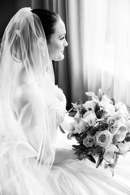 Black and white photo of bride in wedding dress with veil over updo looking out window with bouquet