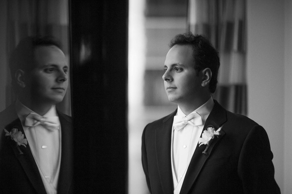 Black and white photo of groom looking at reflection