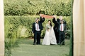 bride in wedding dress by the boutique by b.belle events walking down aisle with cousins brothers