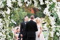 Vow exchange under flower arch greenery orchids groom in bow tie back of officiant