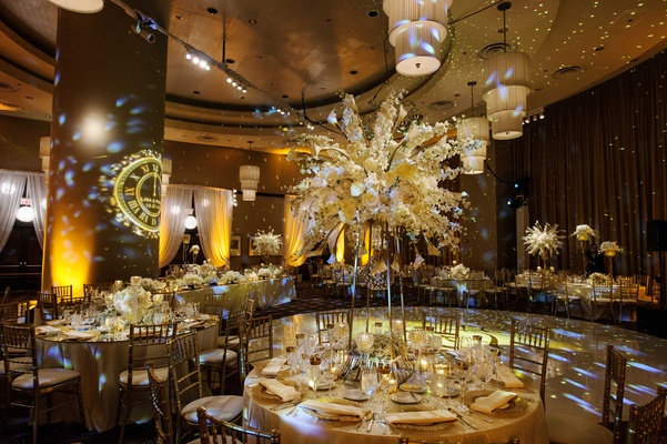 reception space with multiple colorful lights and tall floral arrangements in white and gold