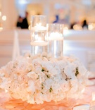 Wedding reception table with pink tablecloth with circle appliques, white flowers around floating