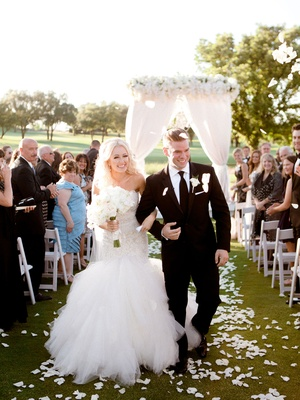 Bride in Eve of Milady wedding dress holding hands with groom in suit with flower petals in air toss