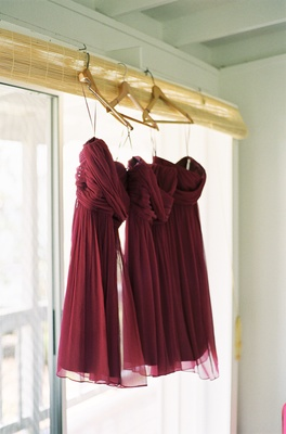 Magenta wine-colored gowns hanging on hangers