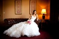 Bride in a Maggie Sottero dress with ruffled skirt and sweetheart neckline and pink bouquet