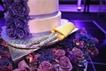 White wedding cake with purple sugar roses, crystals, silver handled cake server set in gold napkin