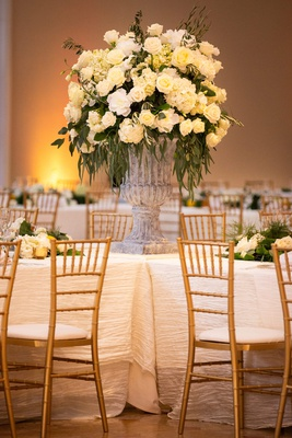 large stone vase with ivory flowers and dark greenery in the center of intersecting tables with