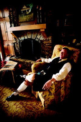 Father of the bride in a Scottish kilt sits on a chair