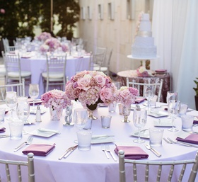 Rooftop wedding reception tables with purple linens, roses, silver chairs