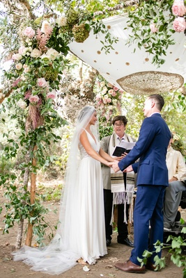 Bride in Jenny Packham dress and Dear Maradee veil holds grooms hands under outdoor chuppah Jewish