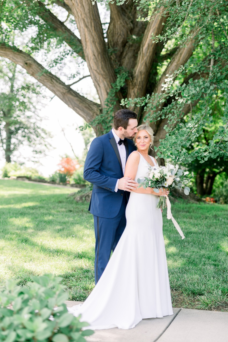 groom in navy blue tuxedo stands behind bride and kisses her on the forehead