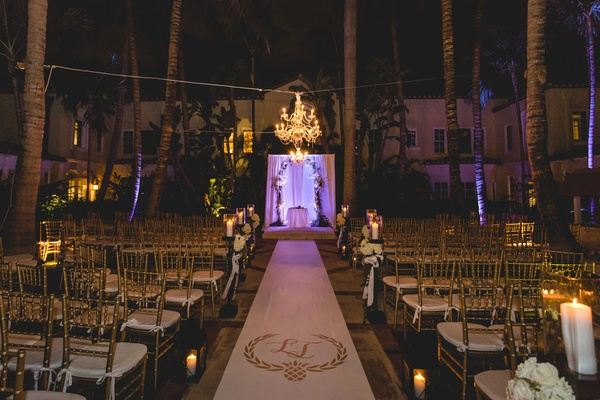 Aisle runner with monogram and violet light at altar palm trees chandelier gold chairs