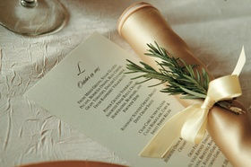 White stationery with black monogram next to gold napkin and rosemary sprig