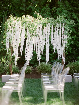 brandin cooks backyard wedding, arbor with greenery and cascading white flowers, ghost chairs