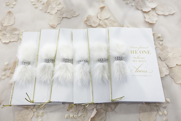 wedding ceremony programs with gold cord, feathers, and crystal