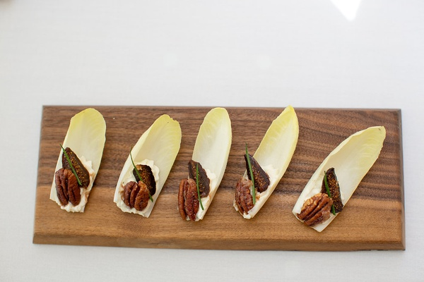 Wood platter of endive leaves topped with goat cheese, caramelized pecans, figs at wedding shower