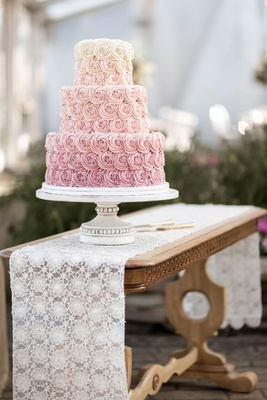 wedding cake three layer on antique vintage inspired cake stand wood table lace runner pink ombre