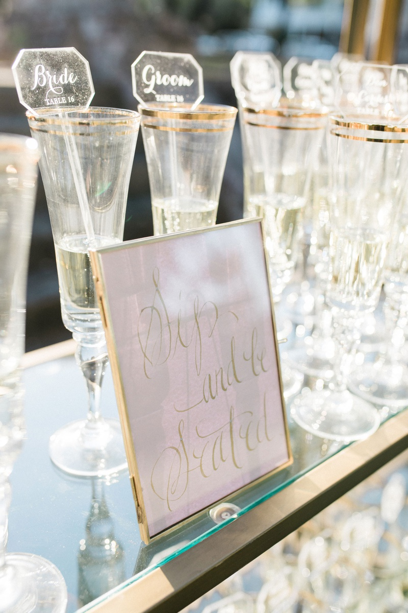 wedding escort cards on acrylic drink stirrers champagne glasses on gold glass bookcase bookshelf