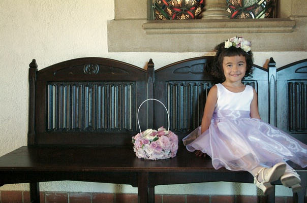 Flower girl sits on bench wearing white and purple dress