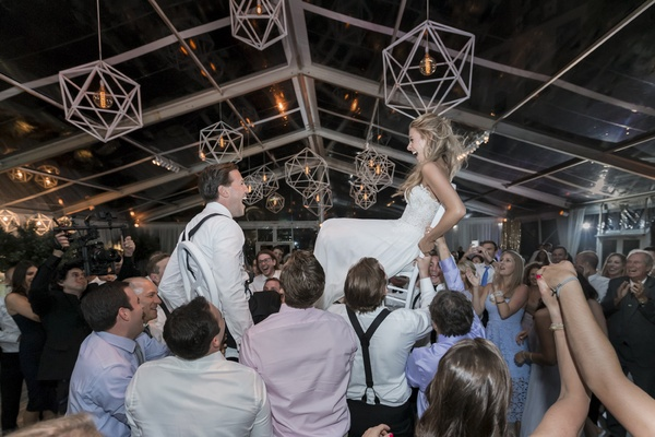 bride and groom lifted on chairs during the hora in a clear-top tent