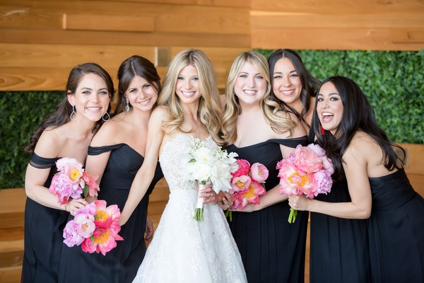 Bride in strapless reem acra wedding dress with bridesmaids black gowns dresses pink coral peony