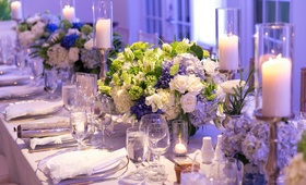 Long wedding reception table with white and blue rose hydrangea centerpieces greenery candles purple