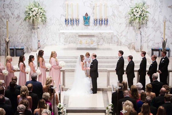 bride and groom wedding ceremony vow exchange bridesmaids and groomsmen on stage at altar flowers