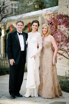 Mother in gold gown with strapless neckline bride in white bridal gown lace illusion long sleeves