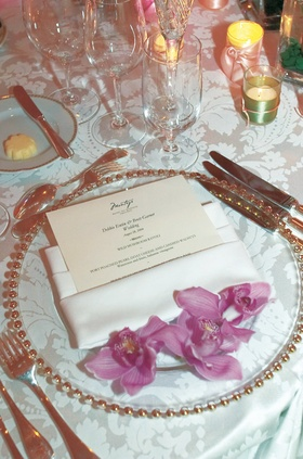 white linens and pink blooms on gold-rimmed charger