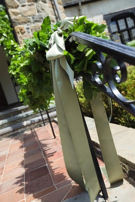 Handrail decorated with an olive green ribbon and greenery garland at a wedding