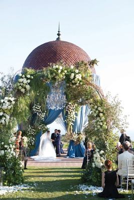 resort at pelican hill wedding with blue drapery on rotunda, arches of floral and greenery