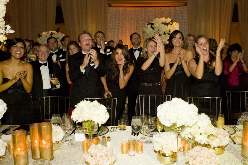 Guests to a black-tie wedding cheer on the bride and groom