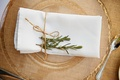 Burlap table runner with gold charger and rosemary