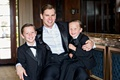 groom with arm around ring bearers, ring bearer sitting on groom's lap