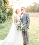 Bride in illusion long sleeve wedding dress veil and groom in grey three piece suit
