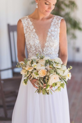 Bride in Mira Zwillinger wedding dress from Carine's Bridal Atelier holding rustic wedding bouquet