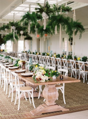 Wedding reception wood pedestal table white chairs with long flower low centerpiece and bottles fern